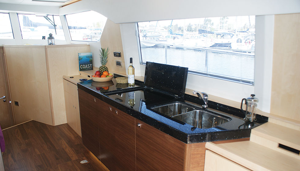 A galley unit, built in the same walnut as the floor, with high-gloss Corian worktop. The hob and sink may be covered when not in use, and behind the doors are a fridge, electric oven and storage