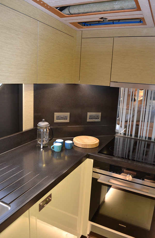 A corner of her comprehensively equipped galley with Corian countertops and high-gloss white units